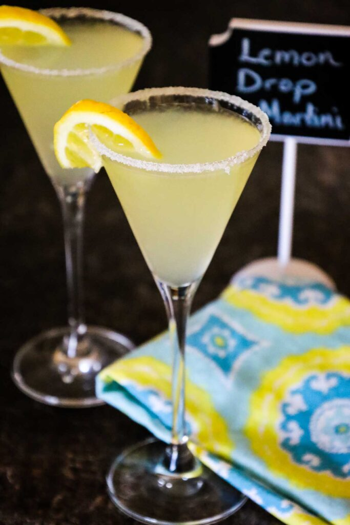 A lemon drop martini in a martini glass with a sugar rim and half of a lemon slice on a dark table with a 3 toned blue, yellow and white napkin, a 2nd martini, and a chalkboard banner with the words Lemon Drop Martini written on it blurred in the background.