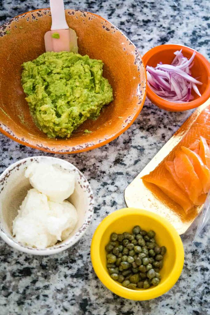 Ingredients from top going clockwise, mashed avocado in an orange bowl, an orange prep bowl with thin slices of red onion, a gold tray with sliced smoked salmon, a yellow prep bowl with green capers, and a white prep bowl with cream cheese.