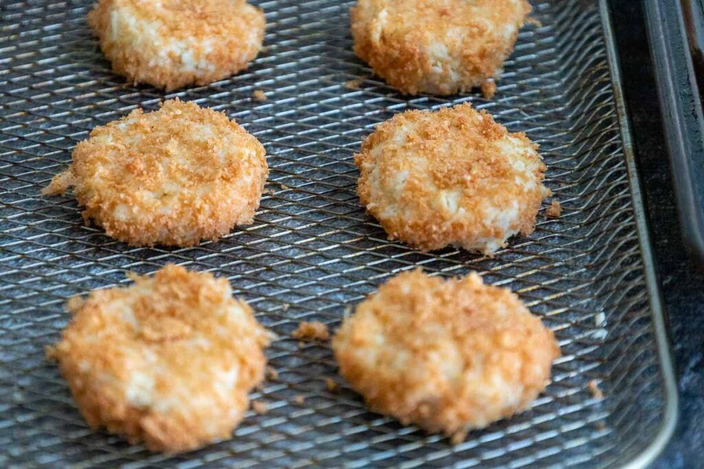nuggets coated with pork rinds on an air fryer tray.