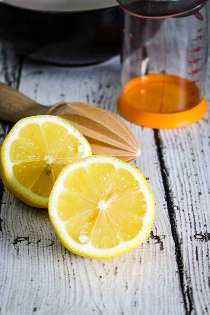 A lemon cut in half with a wooden citrus reamer in the background and a clear measuring cup with an orange bottom rim.