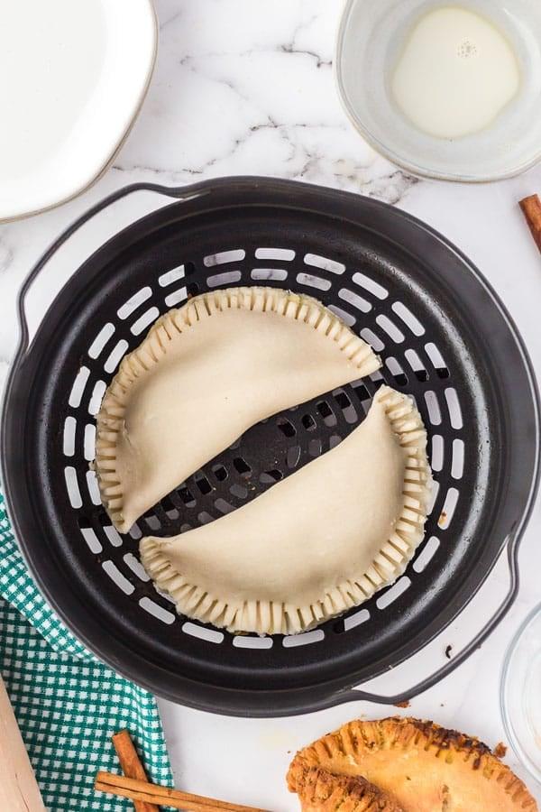 Two pumpkin hand pies in the air fryer basket.