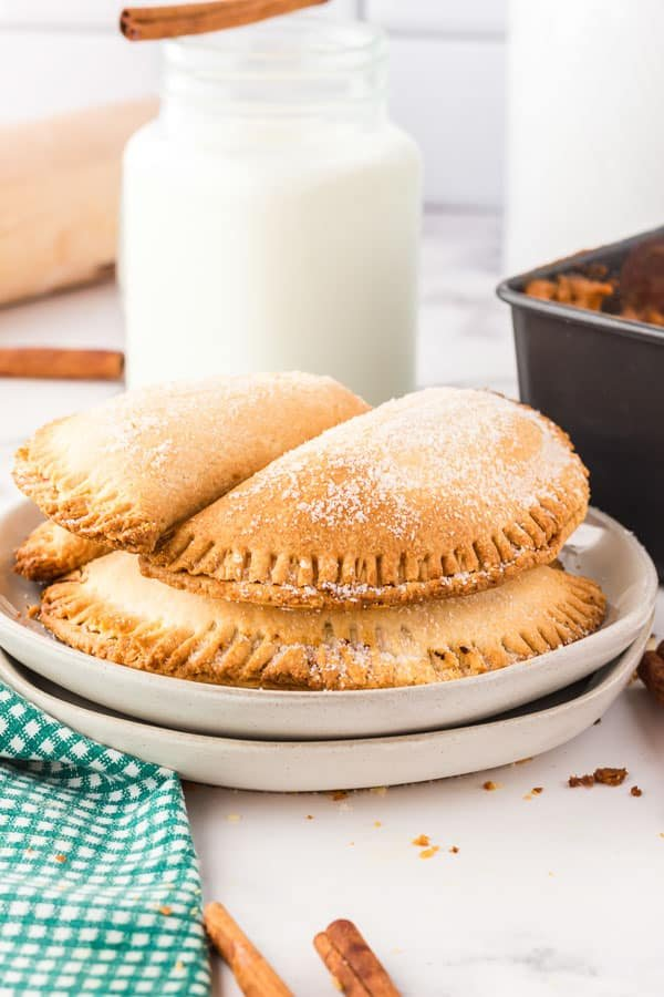 A stack of four air fryer pumpkin hand pies on a white plate with a jug of white milk behind the plate.