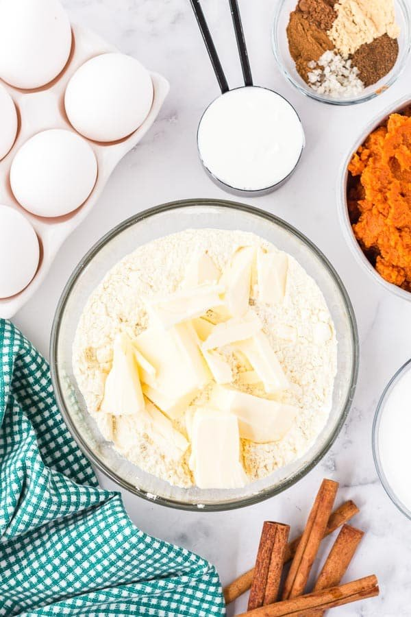 Overhead view of ingredients from 12:00 clockwise Spices, pumpkin flour and butter mixture, cinnamon sticks, and eggs in carton with a green and white checked towel to the bottom left.