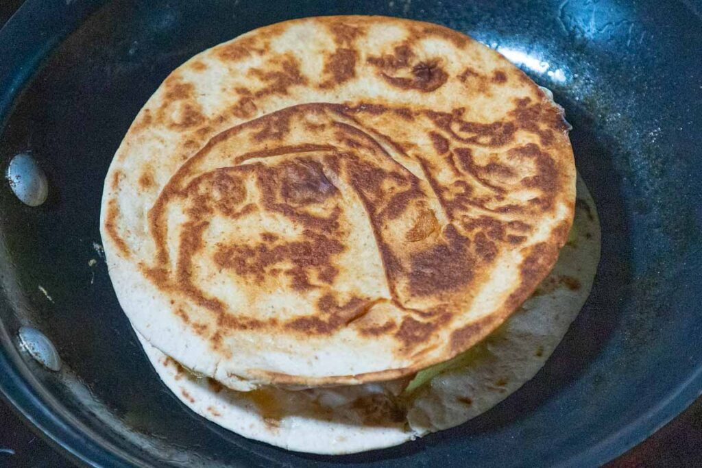 Breakfast quesadillas cooking in a skillet with the top tortilla browned.