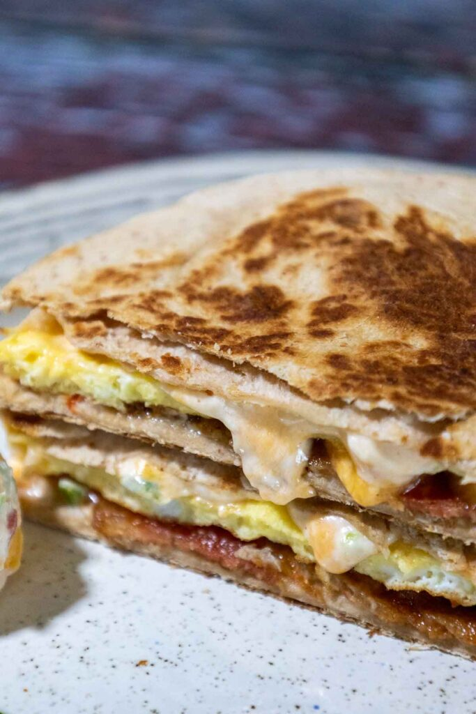 Breakfast quesadillas cut in half so you can see the inside of the quesadilla with bacon on the bottom layer, cooked egg, and pimento cheese melting down the sides of the cut edges with another scoop of pimento cheese to the front left and four jalapeno rings in front of the quesadilla.