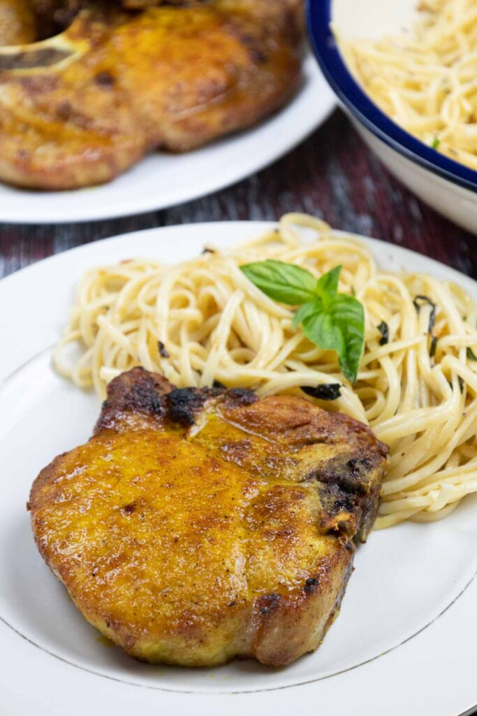 One golden air fryer pork chop on a white plate with a side of pasta topped with fresh basil behind the pork chop. In the back left a platter of pork chops and in the back right a cream colored serving bowl with a blue rim holding cooked linguine topped with basil.