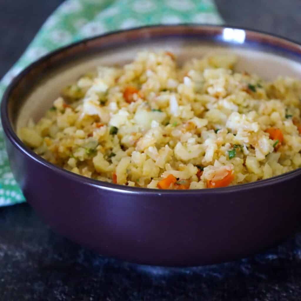 Cauliflower Fried Rice in a brown serving bowl with flecks of orange carrot and green cilantro scattered in the rice.