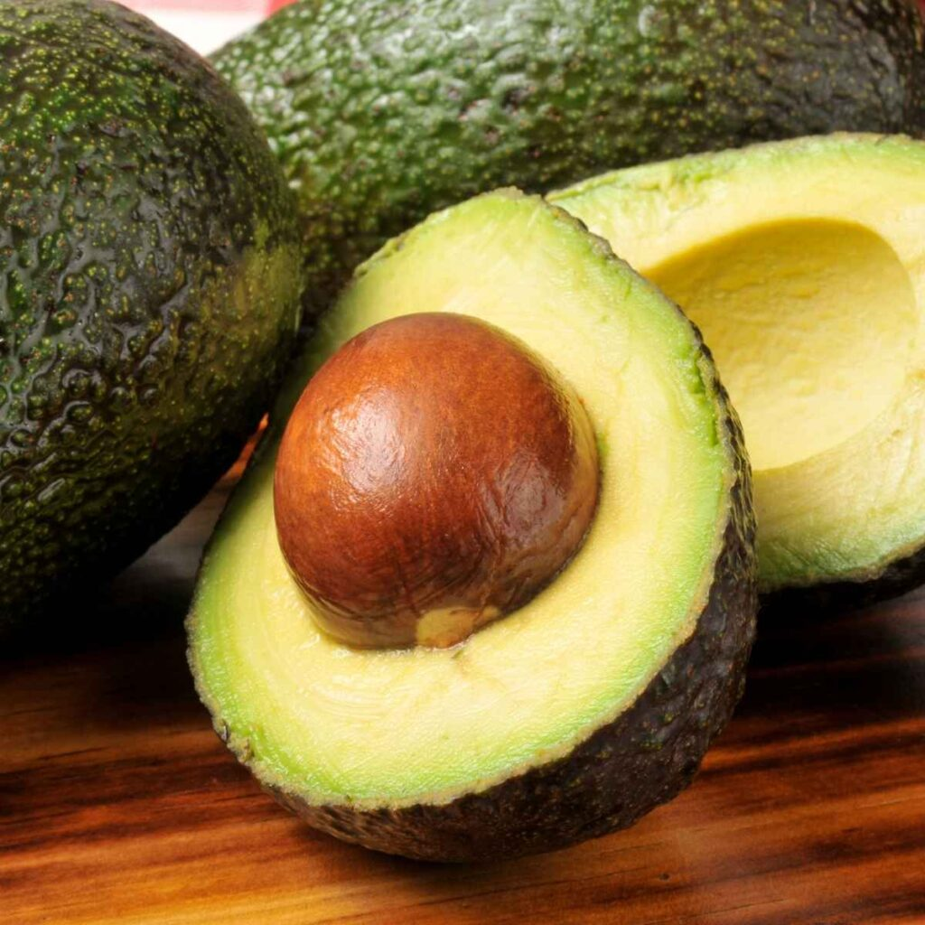 An avocado cut in half with the brown pit still inside one half and the half without the pit behind it with 2 whole avocados in the background on a wooden cutting board.