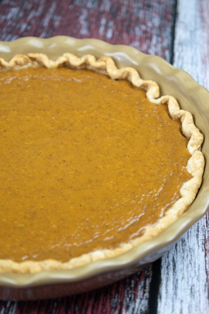 Over head shot of a whole baked pumpkin pie with condensed milk.