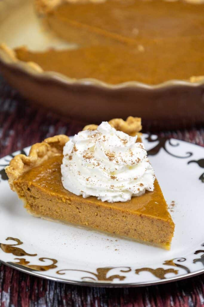 One slice of baked pumpkin pie with condensed milk topped with whipped cream and a sprinkle of spices on a white plate with silver trim.