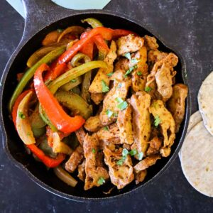 A cast iron skillet with vegan steak fajitas and 3 flour tortillas to the right of the skillet.