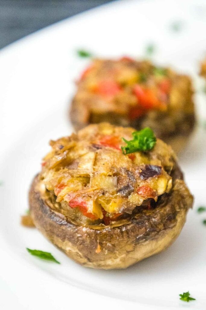 Two cooked stuffed mushrooms on a white plate sprinkled with green parsley with flecks of red pepper and onion showing in the stuffing.
