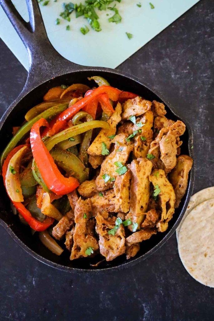 Vegan Steak Fajitas in a black cast iron skillet with steak strips to the right and peppers and onions to the left side with cilantro on top of the fajitas and in the background to the left.