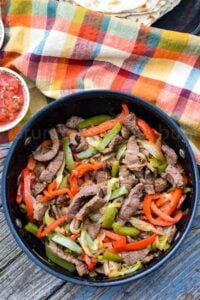 A skillet with venison strips, onion, red and green bell pepper slices.