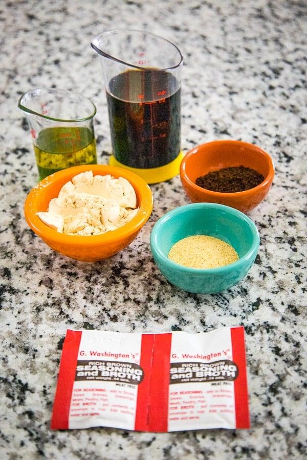 Ingredients from top going clockwise, coconut aminos, vegemite, garlic powder, hickory smoked torula yeast, broth powder, oil,
