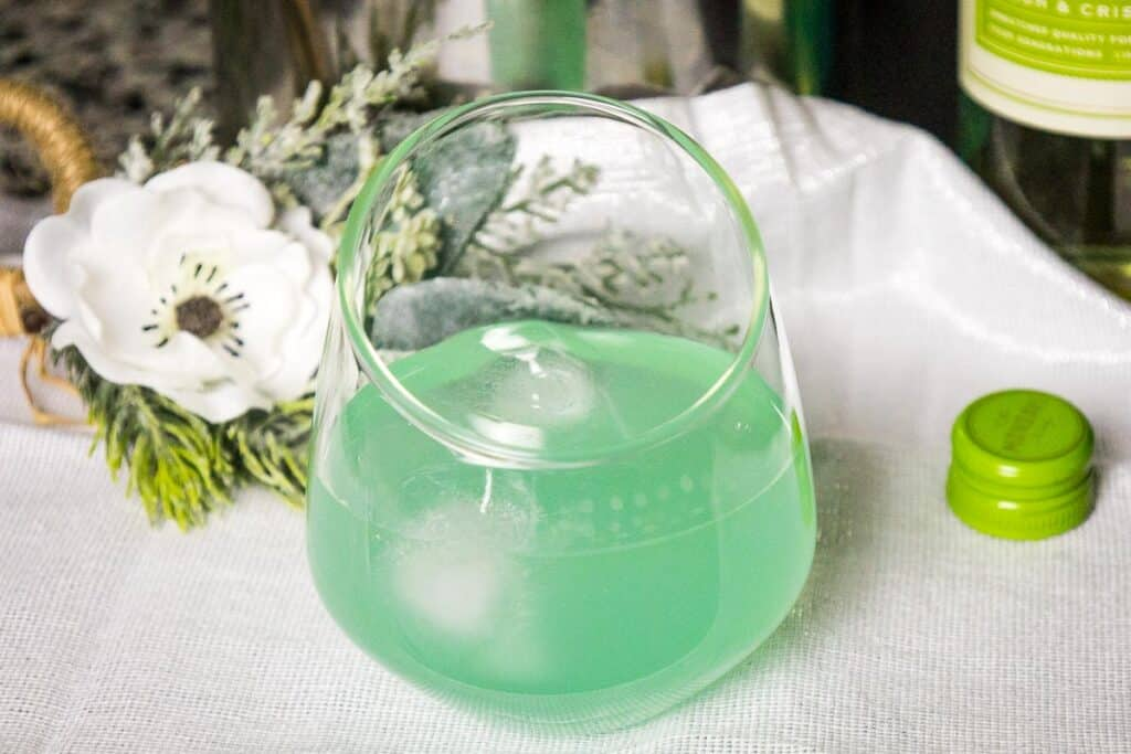 Blue Diamond Wine Cocktail in a clear drink glass on a white napkin with a white rose in the background and green bottle cap beside the glass.