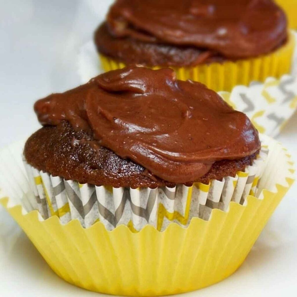 Upclose image of Texas Sheet Cake Cupcakes in a yellow and gray pattern cupcake wrapper.